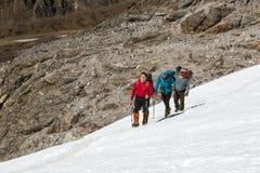 Alpina klättrare som tungt kliver upp på snölutning arkivfoto
