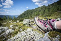 Alpine boots in foreground, idyllic mountain landscape in the blurry background. Cut out of a woman in hiking boots who is enjoying the idyllic mountain royalty free stock image