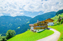 Alpine building with green meadows and high peaks Royalty Free Stock Images