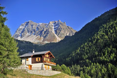 Alpine chalet. An alpine chalet in a forested alpine valley in Switzerland with a mountain peak beyond. Space for text in the clear blue sky Stock Photos