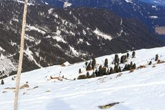 Alpine chalet houses and mountain snow panorama with trees in winter in Stubai Alps Stock Photo