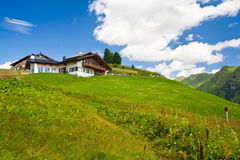 Alpine chalet in mountains. Summer time Royalty Free Stock Images