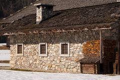 An alpine chalet in wood and stones and little dog house royalty free stock photo