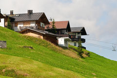 Alpine chalets on hill. Summer time Royalty Free Stock Photos