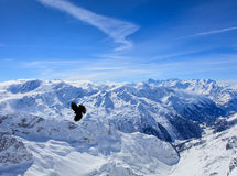 Alpine chough flying over summits of the Swiss Alps. View from Mt. Titlis in winter. The Titlis is a mountain in Switzerland, located on the border between Stock Photo