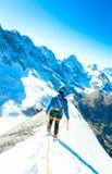 Alpine climber balances on the ice snowfield Stock Image