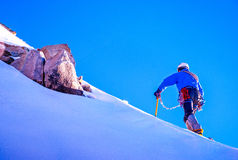 Alpine climber balances on the ice snowfield Royalty Free Stock Photography