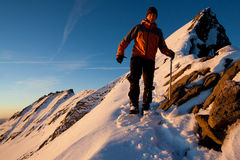 Alpine climbing. Young man on a snow mountain ridge Royalty Free Stock Photo
