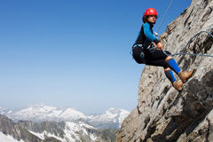 Alpine climbing. Young woman abseiling rock face in the Alps with large copy space stock photo