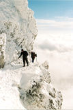Alpine climbing. Two climbers over the clouds in snowy mountains Royalty Free Stock Photo