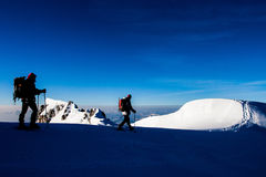 Alpine climbing. Two climbers on a snow ridge in the Alps Stock Images