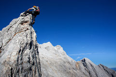 Alpine climbing. Young woman with backpack climbing along sharp alpine ridge Stock Image