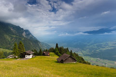 Alpine country houses in Swiss Alps. Under dark clouds. St. Gallen, Switzerland Royalty Free Stock Photos