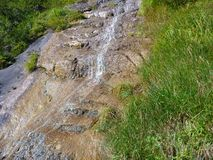 Alpine creek falling down the rock Royalty Free Stock Photo