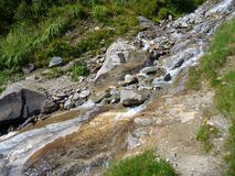 Alpine creek falling down the rock Stock Photo