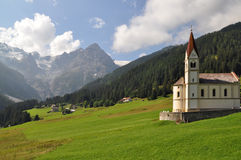 Alpine cultural landscape. Alpine landscape formed by centuries of human utilization with farms houses, pastures and a church stock photos
