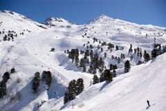Alpine downhill slope. A perspective view on an alpine snow downhill slope with peaks, trees, skiers and snowboarders Stock Photo