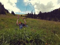 Alpine enviroment at the swiss alps. In summer. On the meadow is a boy playing with a glider stock images