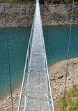 Alpine footbridge over lake. A footbrige over the hydroelectric basin of Morasco, Formazza, Italy Royalty Free Stock Photography