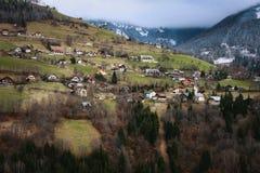 Alpine Frühlingsfelder und traditionelle Holzhäuser stockfotos