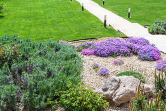 Alpine garden and sloped lawn with path. On backyard of country house Royalty Free Stock Photography