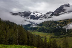 Alpine glacier and peaks of the mountains in the clouds Stock Images