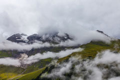Alpine glacier and peaks of the mountains in the clouds Stock Photos