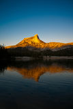 Alpine Glow on Cathedral Peak reflected in the lake Stock Image