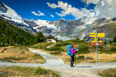 Alpine hiking trails with hikers,Zermatt,Switzerland,Europe. Stunning alpine landscape,hiker woman with backpack,paper map,orientate and find direction in high royalty free stock photography