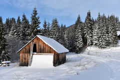 Alpine house covered with snow in the mountains Stock Photos