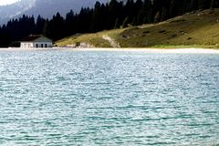 Alpine hut on the shore of a beautiful alpine lake Royalty Free Stock Photography