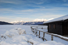 Alpine hut in the snow. A half of an alpine hut with the mountains on the background and the snow all around Stock Photos
