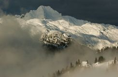 Alpine hut view. Alpine cottages with trees in bacgroung mountain peak Stock Photo