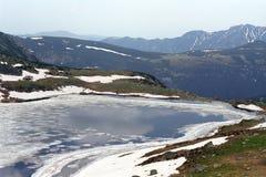 Alpine lake. Frozen mountaine lake on springtime Stock Image