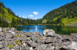 Alpine Lake. Beautiful alpine lake on a sunny day. Lake 22 is nestled in between snow covered mountains and grassy hills in western Washington Stock Image
