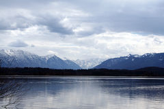 Alpine lake. Lake staffelsee near the bavarian alps in early april when the mountains are still covered with snow royalty free stock image