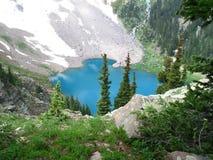 Alpine lake. Mountain lake with trees and snow stock photos