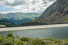 Alpine Lake and Dam with Mountain View Royalty Free Stock Photography