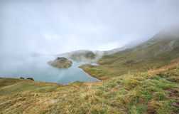 Alpine lake in dence fog Stock Images