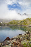 Alpine lake in the fog. Stock Image