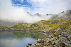 Alpine lake in the fog. Royalty Free Stock Photography