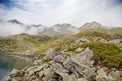 Alpine lake in the fog. Stock Photos