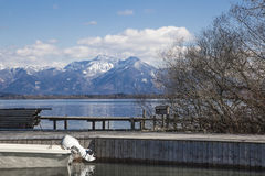Alpine lake Lanscape. A blue sky picture of the Alps taken from a lake in bavaria showing jetty and moored boat in the foreground stock photos