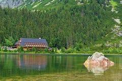 Popradske Pleso mountain lake in High Tatras mountain range in Slovakia. Alpine lake Popradske pleso with touristic shelter - Chata pri popradskom plese royalty free stock images