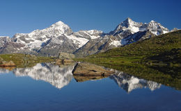 Alpine lake with reflection of mountains in water Royalty Free Stock Images
