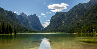 Alpine lake with valley in the back. Alpine lake comming from the valley, Lago di Landro, Italy Royalty Free Stock Images
