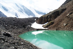 Alpine Lake. With water color blue. In the background the snowy mountain peaks Stock Photography