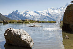 Alpine lake with waterfall Stock Photo