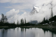 Alpine lake in winter. Snow alpine peak and cloudy alke view Royalty Free Stock Photography