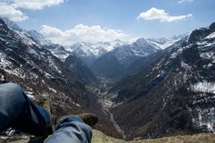 Alpine landscape. Scenic view of mountainous alpine landscape with feet of person relaxing in foreground Royalty Free Stock Photos